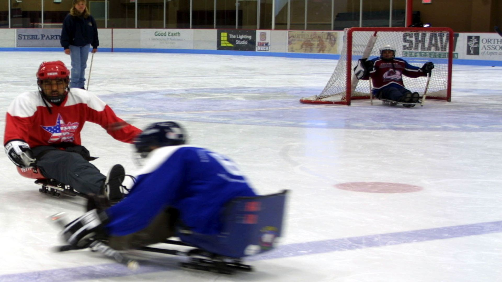 Sgt. Erick Castro faces a member of the opposing team in a sled hockey game. Castro, who lost his left leg at the hip in an ambush last year near Fallujah, tried the sport for the first time in the annual National Disabled Veterans Winter Sports Clinic, held April 4-9 near Aspen.